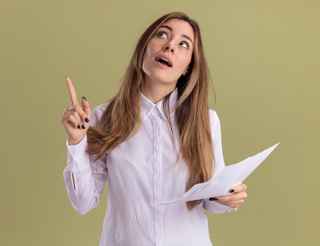 Surprised young pretty caucasian girl holds blank paper sheets looking and pointing up isolated on olive green wall with copy space
