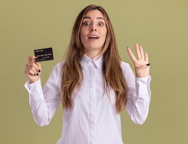 La giovane ragazza piuttosto caucasica sorpresa tiene la carta di credito e fa quattro gesti con le dita