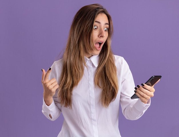 La giovane ragazza piuttosto caucasica sorpresa tiene e guarda il telefono rivolto verso l'alto isolato sulla parete viola con spazio di copia