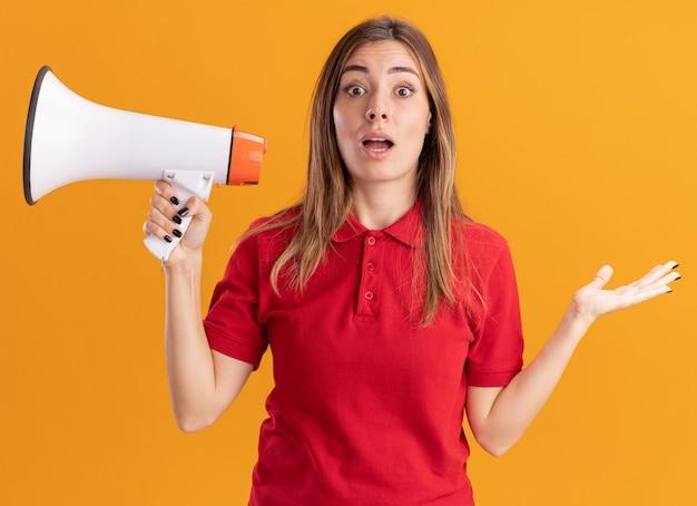 La giovane ragazza abbastanza caucasica sorpresa tiene l'altoparlante e tiene la mano aperta sull'arancio