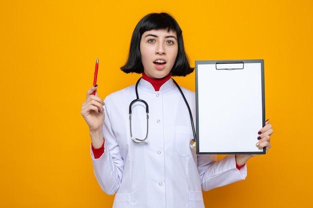 ペンとクリップボードを保持している聴診器を持つ医者の制服を着た驚くべき若いかなり白人の女の子