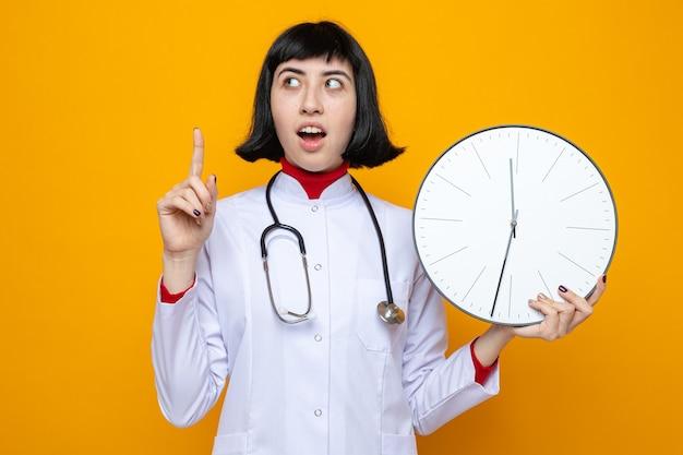 청진기를 가리키고 시계를 들고 있는 의사 유니폼을 입은 놀란 젊은 백인 소녀