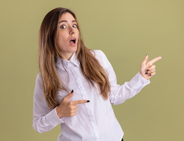 驚いた若いかなり白人の女の子は、コピースペースのあるオリーブグリーンの壁に分離された両手で横を指しています