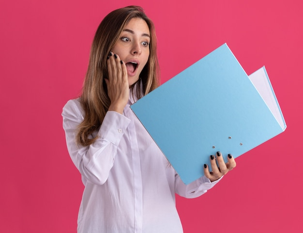 Surprised young pretty caucasian girl puts hand on face holding and looking at file folder on pink