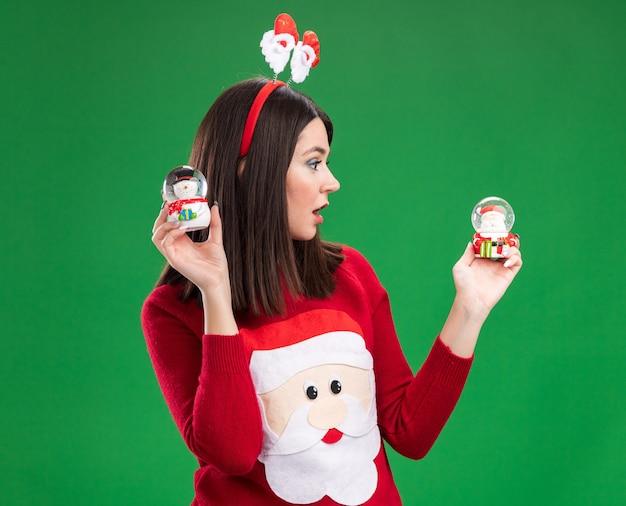 Удивленная молодая симпатичная кавказская девушка в свитере санта-клауса и повязке на голову держит фигурки санта-клауса и снеговика, глядя на фигурку санта-клауса, изолированную на зеленой стене