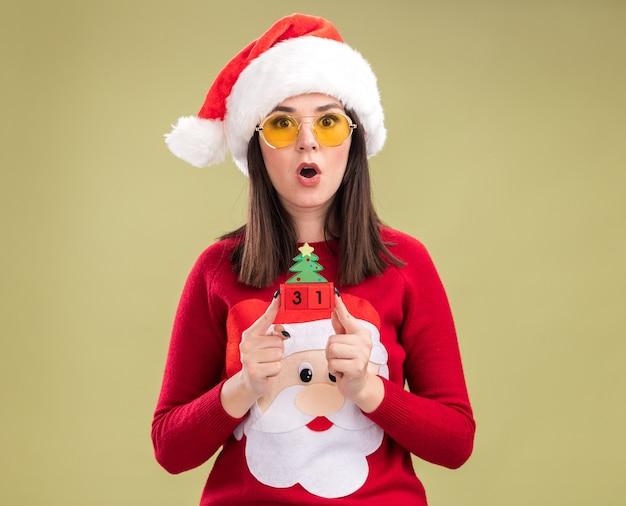 Удивленная молодая симпатичная кавказская девушка в свитере санта-клауса и ободке с очками, держащая елочную игрушку с датой, смотрящую в камеру, изолированную на оливково-зеленом фоне