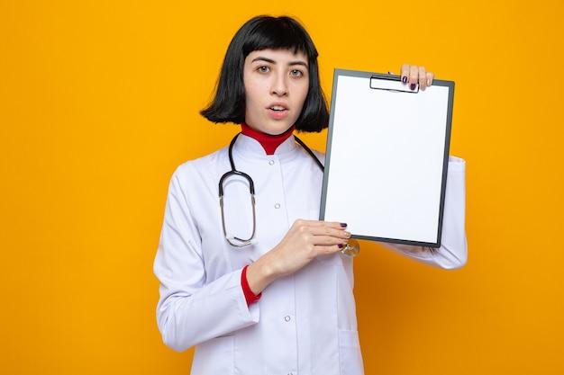 Giovane donna abbastanza caucasica sorpresa in uniforme del medico con la lavagna per appunti della tenuta dello stetoscopio