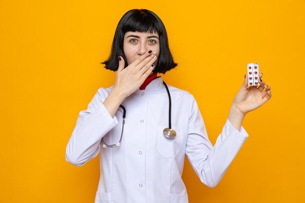 Удивленная молодая симпатичная кавказская женщина в врачебной форме со стетоскопом, прикрывающая рот рукой и держащая таблетки