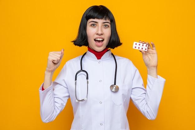 Удивленная молодая симпатичная кавказская женщина в врачебной форме со стетоскопом, указывающим назад и держащим таблетки