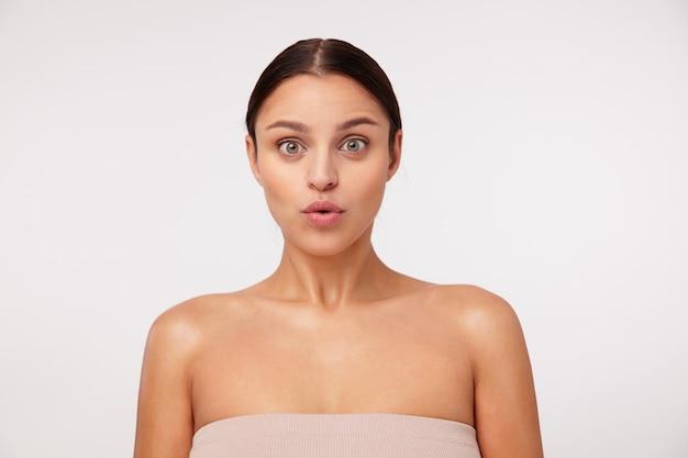 驚いたように見え、眉を上げ、裸の肩でポーズをとっている自然なメイクで驚いた若いかなり黒髪の緑色の目の女性
