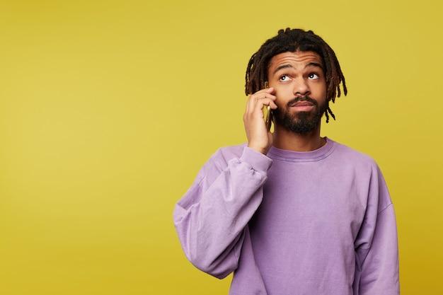 Surprised young pretty dark skinned brunette guy with dreadlocks raising wonderingly eyebrows while having phone call, wearing purple sweatshirt over yellow background