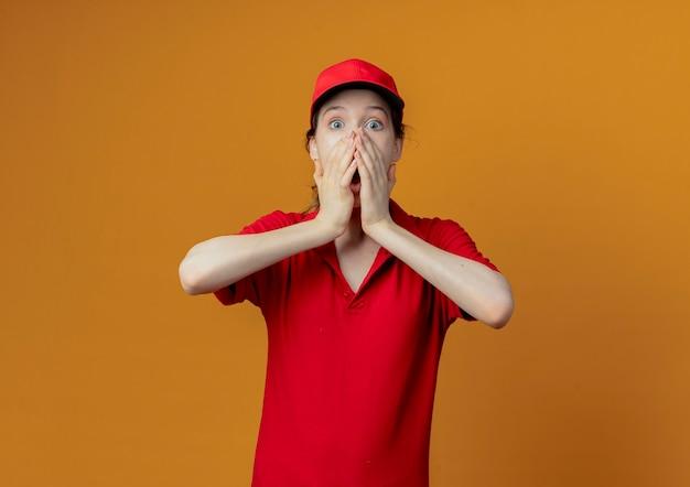 Giovane ragazza graziosa di consegna sorpresa in uniforme rossa e cappuccio che mette le mani sulla bocca che guarda l'obbiettivo isolato su fondo arancio con lo spazio della copia