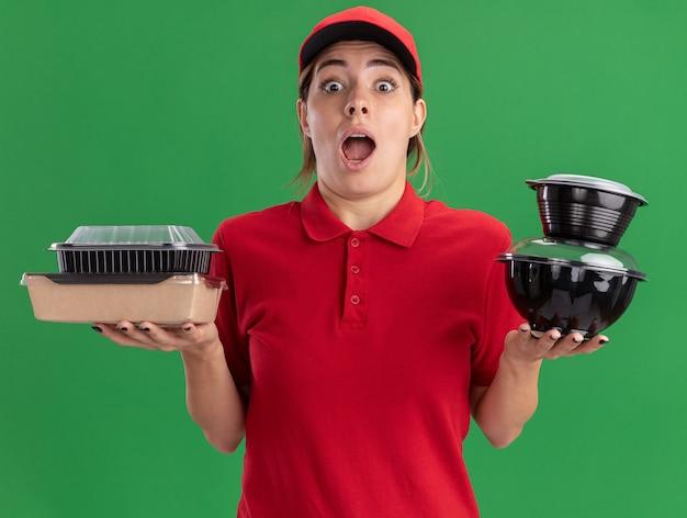 La giovane ragazza graziosa di consegna sorpresa in uniforme tiene i contenitori per alimenti sul verde