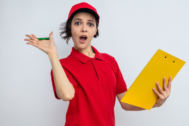 Sorpresa giovane bella donna di consegna che tiene appunti e penna