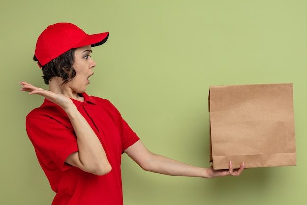 Surprised young pretty delivery woman holding and looking at paper food bag standing with raised hand