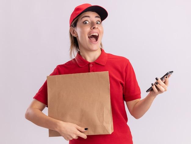 Удивленная молодая красивая женщина-доставщик в униформе держит бумажный пакет и телефон, изолированные на белой стене