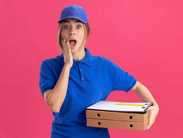 Удивленная молодая красивая женщина-доставщик в униформе кладет руку на лицо и держит буфер обмена коробки для пиццы, изолированный на розовой стене