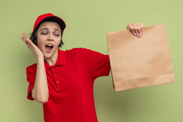 Surprised young pretty delivery woman putting hand on her face and holding paper food packaging