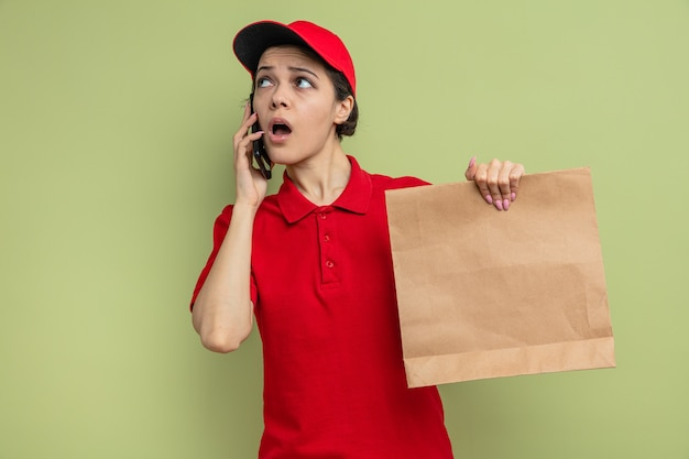 Surprised young pretty delivery woman talking on phone and holding paper food packaging looking at side