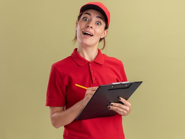 La giovane donna graziosa di consegna sorpresa in uniforme tiene la lavagna per appunti e la penna isolate sulla parete verde oliva