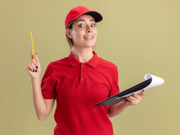 La giovane donna graziosa sorpresa di consegna in uniforme tiene la matita ed i appunti isolati