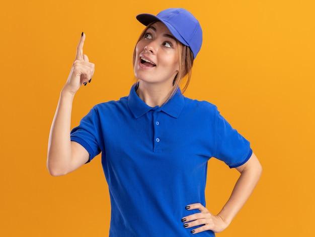 Giovane donna graziosa di consegna sorpresa in punti uniformi e guarda in alto isolato sulla parete arancione