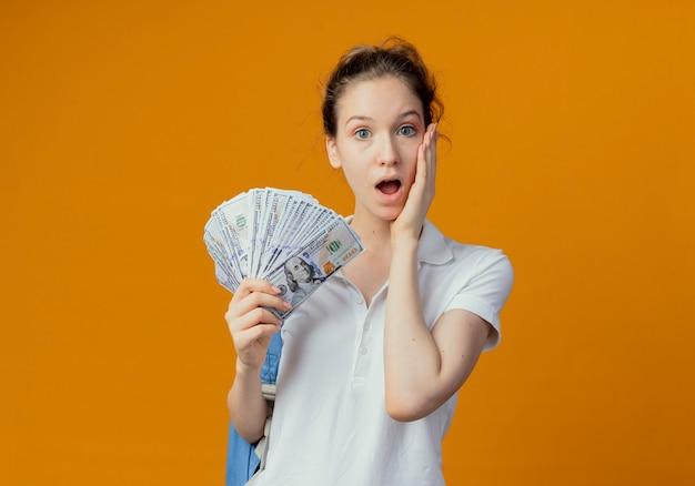 Sorpreso giovane studentessa graziosa che indossa la borsa indietro tenendo i soldi e mettendo la mano sulla guancia