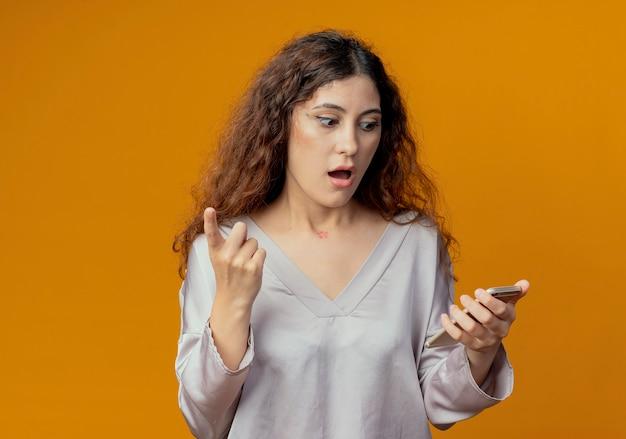 놀란 된 젊은 예쁜 여자 잡고 전화와 포인트를보고 노란색 벽에 고립