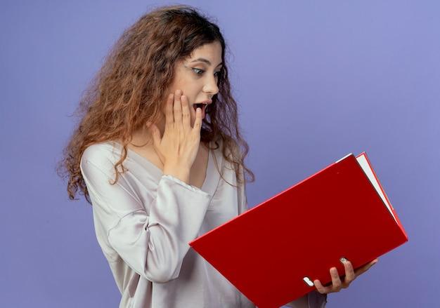 Giovane ragazza graziosa sorpresa che tiene e che esamina la cartella e che mette la mano sulla guancia isolata sulla parete blu