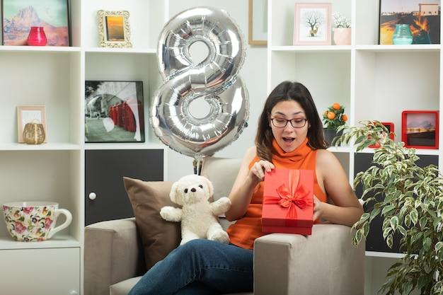 Удивленная молодая красивая девушка в оптических очках открывает и смотрит на подарочную коробку, сидя на кресле в гостиной в международный женский день в марте