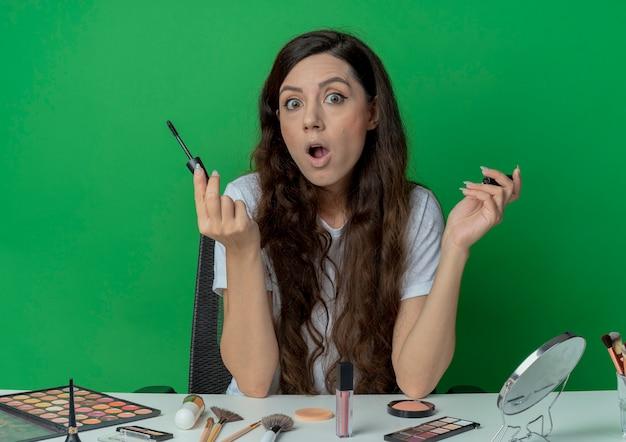 녹색 배경에 고립 된 마스카라를 들고 메이크업 도구와 메이크업 테이블에 앉아 놀란 된 젊은 예쁜 여자