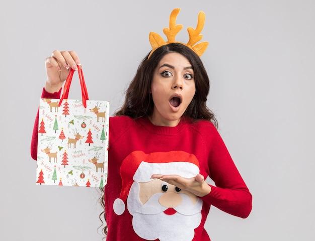 Удивленная молодая красивая девушка в головной повязке с оленьими рогами и свитере санта-клауса держит и указывает на рождественский подарочный пакет, глядя