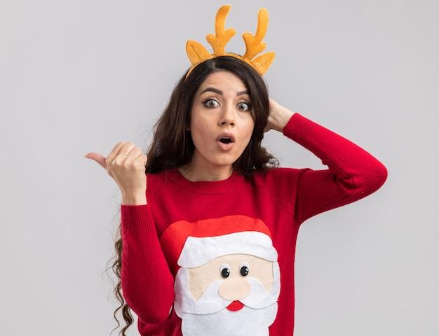 Удивленная молодая красивая девушка в повязке на голову с оленьими рогами и свитере санта-клауса смотрит, держа руку на голове, указывая в сторону