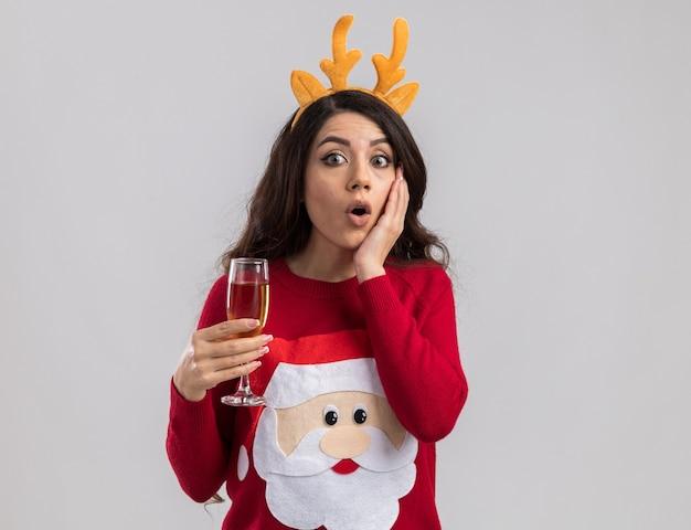 Giovane bella ragazza sorpresa che indossa la fascia di corna di renna e maglione di babbo natale che tiene un bicchiere di champagne guardando tenendo la mano sul viso