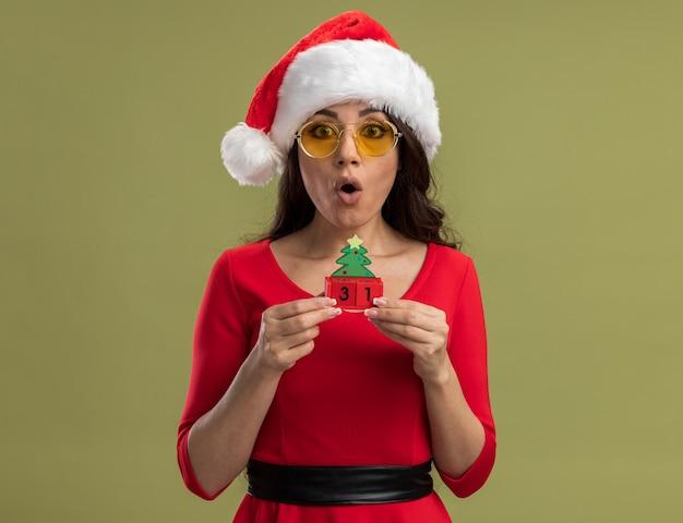 Giovane bella ragazza sorpresa che indossa cappello e occhiali da babbo natale che tengono il giocattolo dell'albero di natale con la data isolata sul muro verde oliva