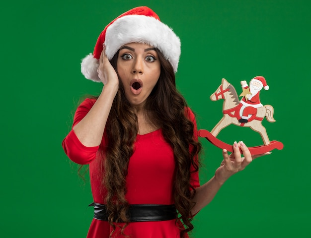 Surprised young pretty girl wearing santa hat holding santa on rocking horse figurine keeping hand on head looking at camera isolated on green background