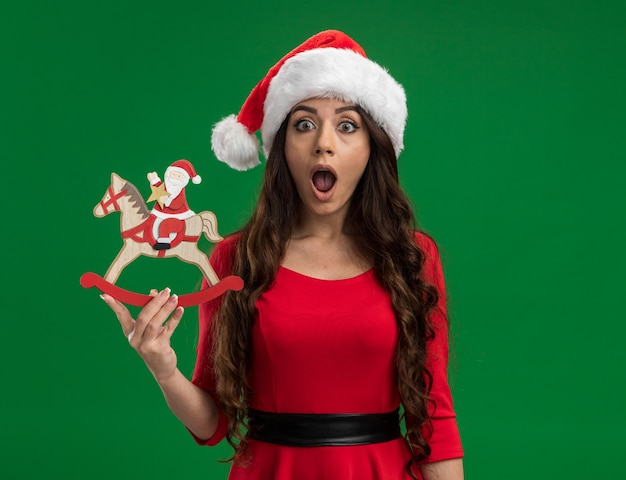 Surprised young pretty girl wearing santa hat holding santa on rocking horse figurine looking at camera isolated on green background with copy space