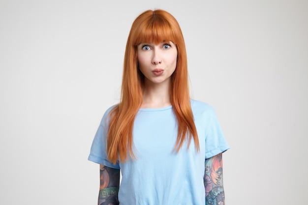 흰색 배경 위에 절연 카메라를 궁금해하는 동안 그녀의 입술을 삐죽 캐주얼 헤어 스타일로 놀란 젊은 꽤 긴 머리 빨간 머리 여자,