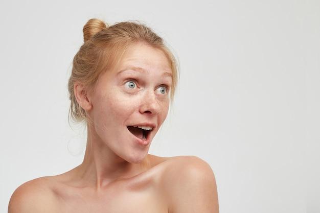 目を大きく開いて口を開けて驚くほど脇を向いて、裸の肩で白い背景の上にポーズをとって、お団子の髪型を持つ驚いた若いかわいい赤毛の女性