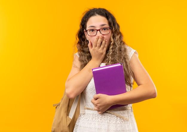 Giovane studentessa graziosa sorpresa con gli occhiali e borsa posteriore che tiene il libro che mette la mano sulla bocca isolata sulla parete gialla