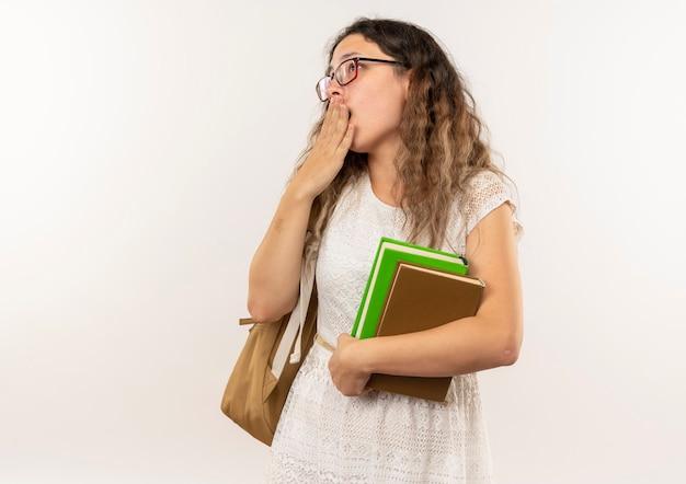 Giovane studentessa graziosa sorpresa con gli occhiali e borsa posteriore che tengono i libri che cercano con la mano sulla bocca isolata sulla parete bianca