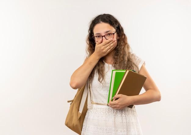 Giovane studentessa graziosa sorpresa con gli occhiali e borsa posteriore che tengono i libri che mettono la mano sulla bocca isolata sulla parete bianca