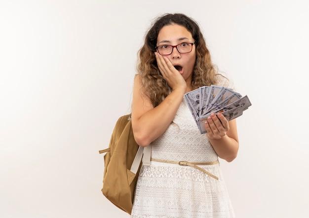 Sorpreso giovane studentessa graziosa con gli occhiali e borsa posteriore che tengono i soldi con la mano sul viso isolato sul muro bianco
