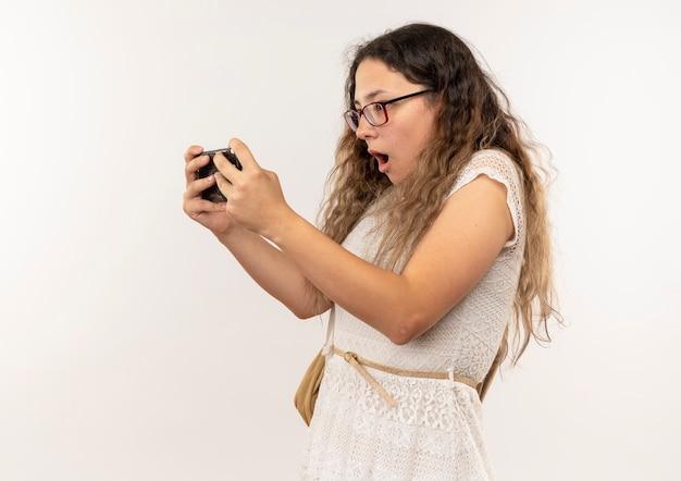 Sorpreso giovane studentessa graziosa con gli occhiali e borsa posteriore utilizzando il suo telefono isolato sulla parete