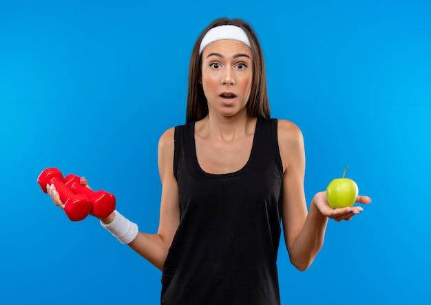 Giovane ragazza abbastanza sportiva sorpresa che indossa la fascia e il braccialetto che tengono i manubri e la mela isolati sullo spazio blu