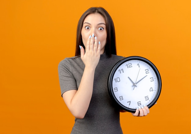 Surprised young pretty woman holding clock and keeping hand on mouth isolated on orange background with copy space