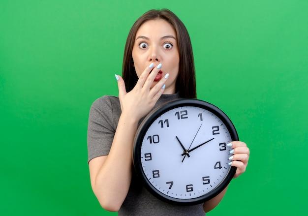 Удивленная молодая красивая женщина, держащая часы, положив руку на рот, изолирована на зеленом фоне с копией пространства