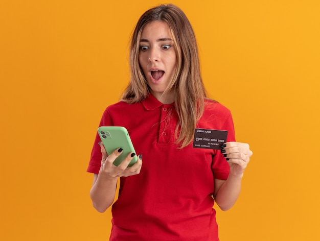 Surprised young pretty woman holds credit card and looks at phone isolated on orange wall