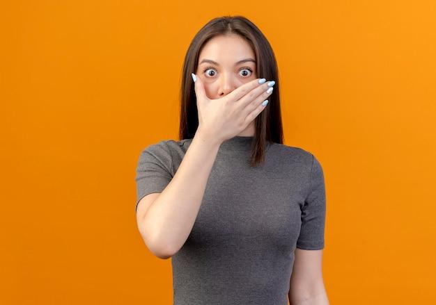 복사 공간 오렌지 배경에 고립 입에 손을 넣어 놀란 된 젊은 예쁜 여자