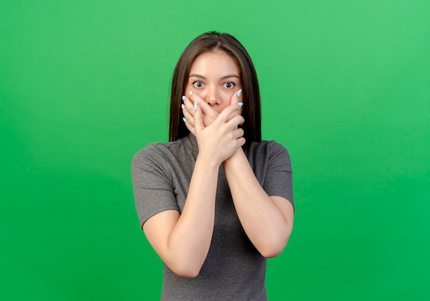 Surprised young pretty woman putting hands on mouth isolated on green background with copy space